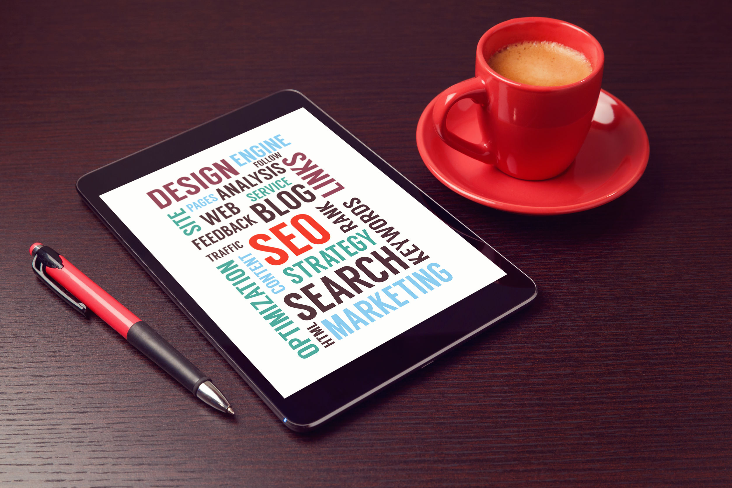 Digital tablet with seo words and coffee cup on office desk